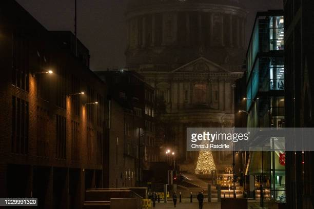 Christmas tree stands in front of St Pauls Cathedral on a foggy morning in England on December 7, 2020 in London, United Kingdom. London is currently...