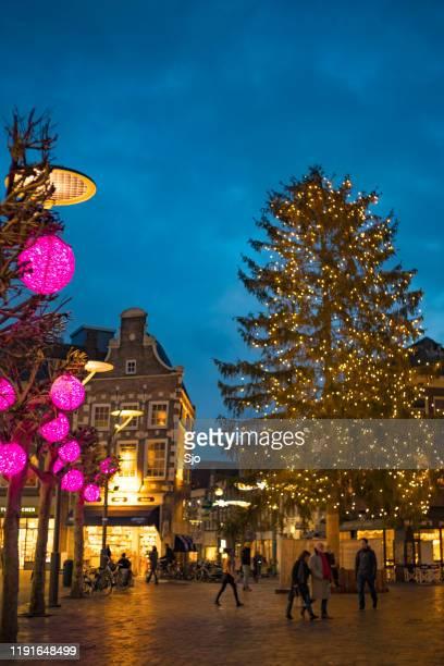 kerstboom met decoraties op de grote markt en de diezestraat winkelstraat 's avonds in zwolle - benelux stockfoto's en -beelden