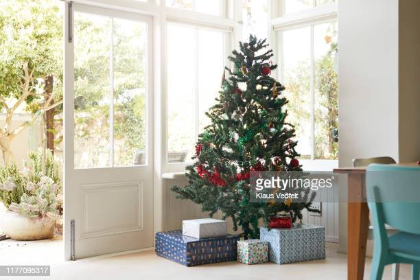 christmas tree with gift boxes by window at home - christmas trees stock pictures, royalty-free photos & images