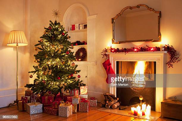 christmas tree with gifts near fireplace - christmas tree stock pictures, royalty-free photos & images