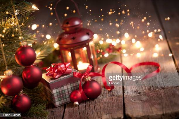 christmas tree with gifts, ornaments and a lantern on an old wood background - christmas decore candle stock pictures, royalty-free photos & images