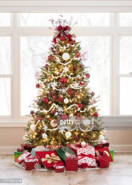christmas tree with ornaments and gifts against a picture window - christmas trees stock pictures, royalty-free photos & images
