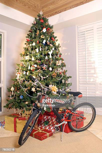 Christmas tree with presents sitting and a red bicycle in corner of living room.