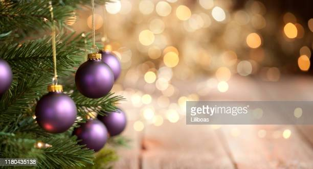 christmas tree with purple baubles and gold lights background - illuminated stock pictures, royalty-free photos & images