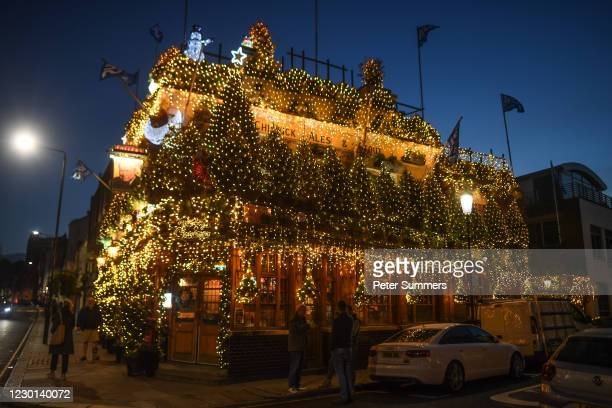 Christmas trees and fairy lights adorn the exterior of the Churchill Arms pub, ahead of London being moved into 'Tier 3' of the pandemic-control...