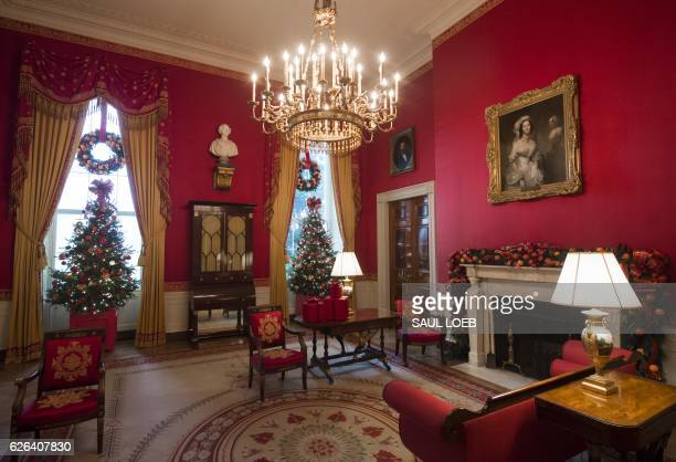 Christmas trees and holiday decorations in the theme of 'The Gift of the Holidays' are seen in the Red Room of the White House in Washington DC...