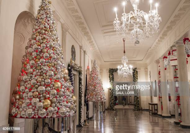 Christmas trees and holiday decorations in the theme of 'The Gift of the Holidays' are seen outside in Cross Hall of the White House in Washington DC...