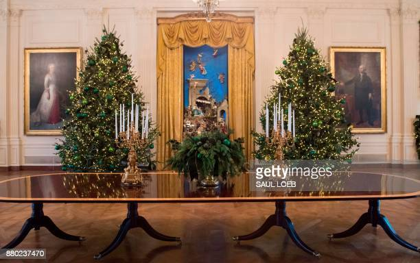 Christmas trees are seen during a preview of holiday decorations in the East Room of the White House in Washington DC November 27 2017 / AFP PHOTO /...