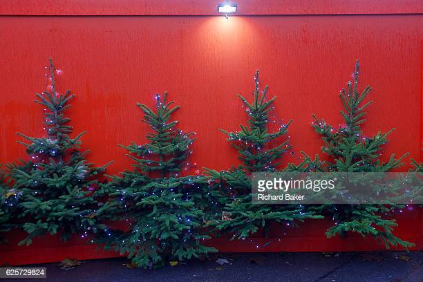 Christmas trees attached to a red hoarding near an Xmas theme village on London's Southbank on 21st November 2016 London England