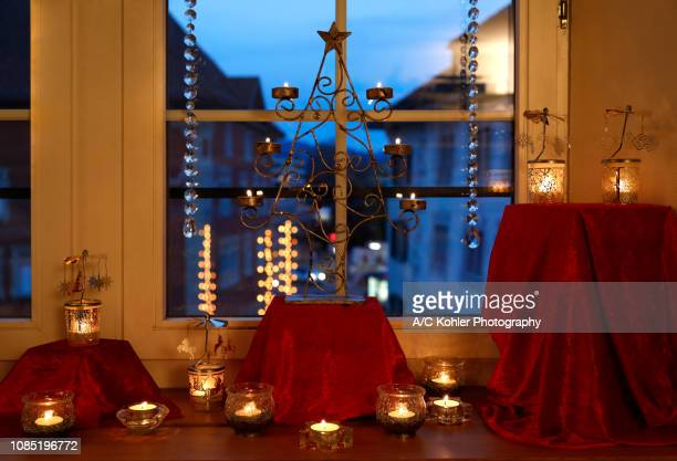 Christmas window decoration with candlelight and Christmas lighting in the background
