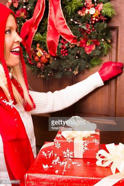 Natale: Donna Bussa alla porta per offrire regali per le feste.