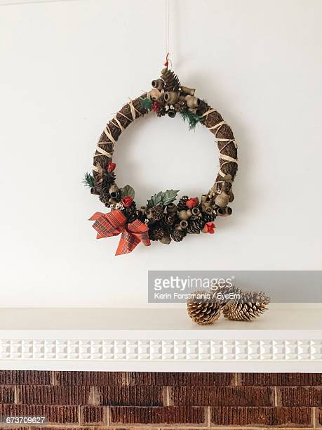 Christmas Wreath Hanging By Pine Cones On White Wall At Home