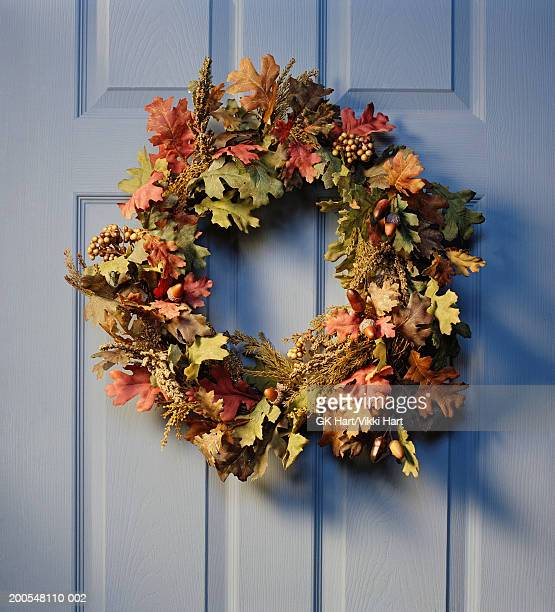 christmas wreath hanging on front door, close-up - autumn decoration stock pictures, royalty-free photos & images