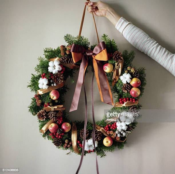 Christmas wreath held by a woman's hand