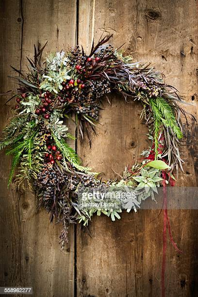 Christmas wreath with foliage and berries on wooden door