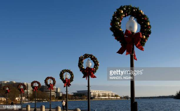 Christmas wreaths adorn the tops of lamppost at the Georgetown waterfront in Washington, DC on December 9, 2020.