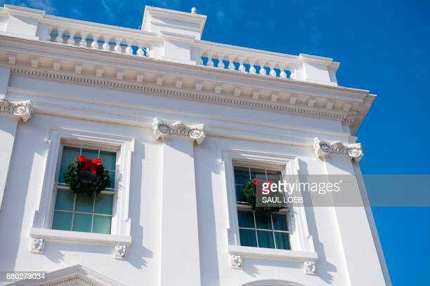 Christmas wreaths hang from the windows during a preview of holiday decorations at the White House in Washington DC November 27 2017 / AFP PHOTO /...