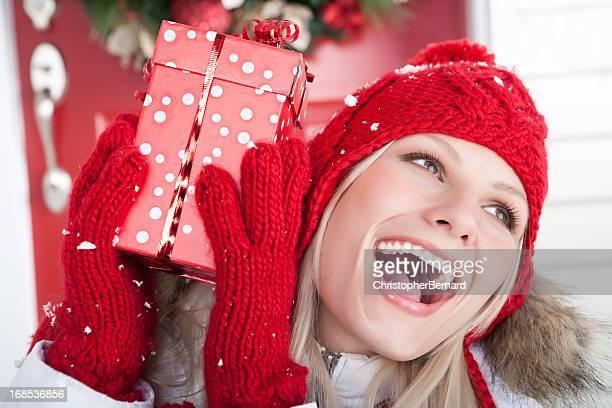 Noël-femme souriante tenant présents à l'extérieur