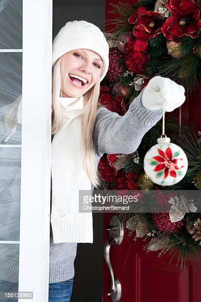Christmas-Smiling woman throwing snowball at front door