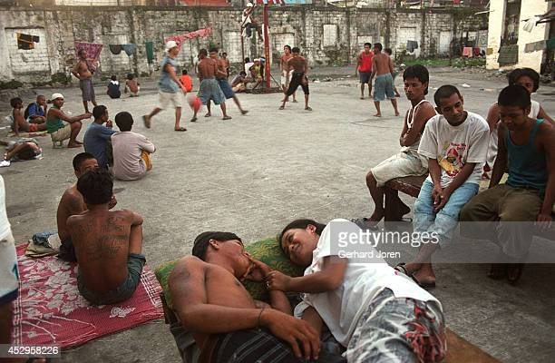 Christo Pyer and his girlfriend Lesel on a bed in the courtyard, while other inmates watch. Christo is a gang member of BCJ . The BCJ is one of 4...