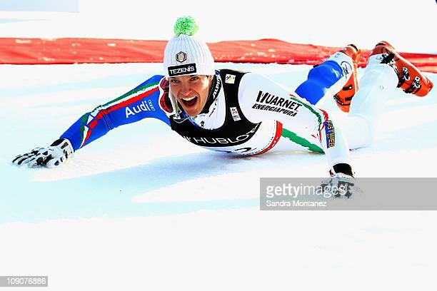 Christof Innerhofer of Italy does a penguin dive in celebration at the flower ceremony after skiing in the Slalom segment on his way to finishing...