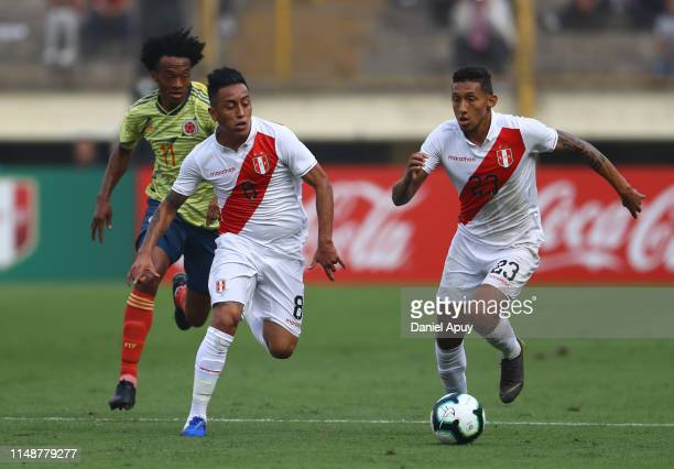 Christofer Gonzales and Christian Cueva of Peru run for the ball during a friendly match between Peru and Colombia at Estadio Monumental on June 9,...
