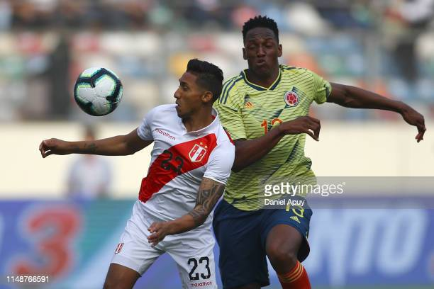 Christofer Gonzales and Yerry Mina compete for the ball during a friendly match between Peru and Colombia at Estadio Monumental on June 9, 2019 in...