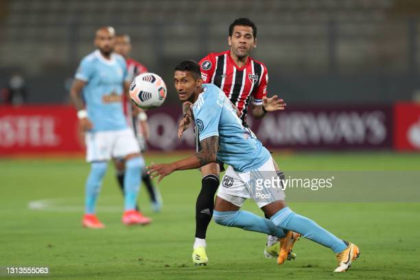 Christofer Gonzalez of Sporting Cristal fights for the ball with Dani Alves of Sao Paulo during a match between Sporting Cristal and Sao Paulo as...