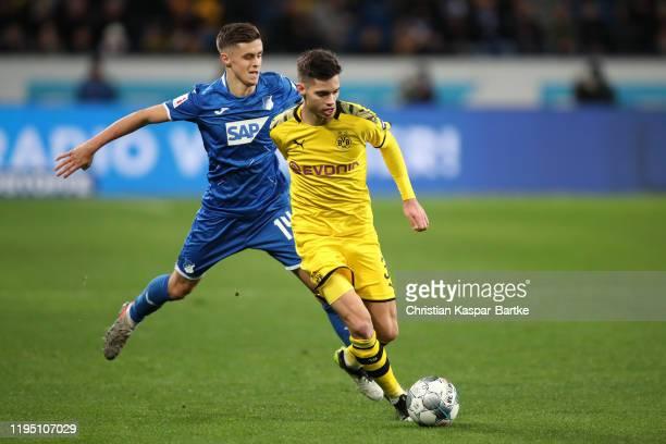 Christoph Baumgartner of TSG 1899 Hoffenheim attempts to tackle Julian Weigl of Borussia Dortmund and during the Bundesliga match between TSG 1899...