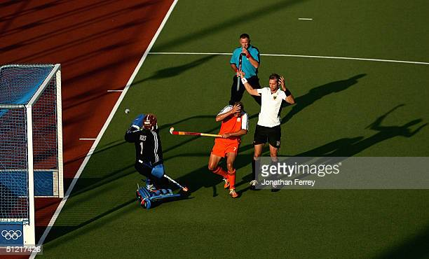 Christoph Bechmann of Germany tries to defends Sander van der Weide of the Netherlands who was hit by the ball in the men's field hockey semifinals...