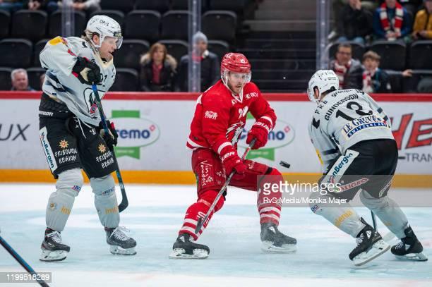 Christoph Bertschy of Lausanne HC battles for the puck with Flavio Schmutz of HC FribourgGotteron and Ryan Gunderson of HC FribourgGotteron during...