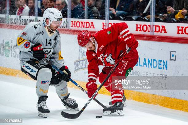 Christoph Bertschy of Lausanne HC battles for the puck with Ralph Stalder of HC FribourgGotteron during the Swiss National League game between...