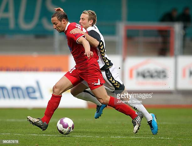 Christoph Burkhard of Burghausen battles for the ball with Andreas Spann of Heidenheim during the third division match between Wacker Burghausen and...