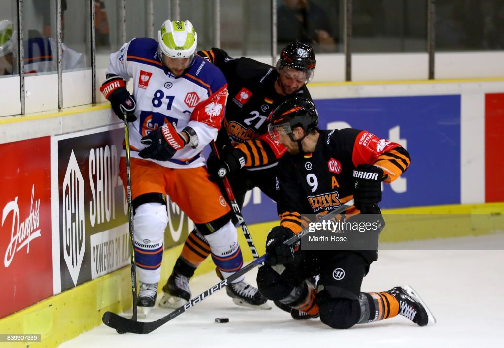 Christoph Hoehenleitner #21 and Jeff Likens of Wolfsburg and Jukka Peltola of Tampere battle for the puck during the Champions Hockey League match between Grizzlys Wolfsburg and Tappara Tampere at Eis Arena Wolfsburg on August 27, 2017 in Wolfsburg, Germany.