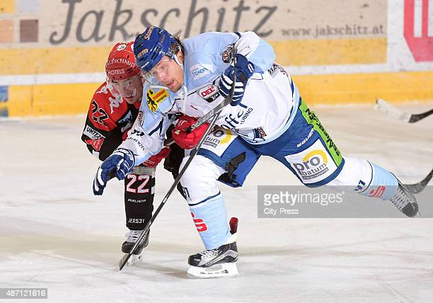 Christoph Hoertnagl of HC TWK Innsbruck and Rene Roethke of Straubing Tigers fight for the puck during the game between HC TWK Innsbruck and...