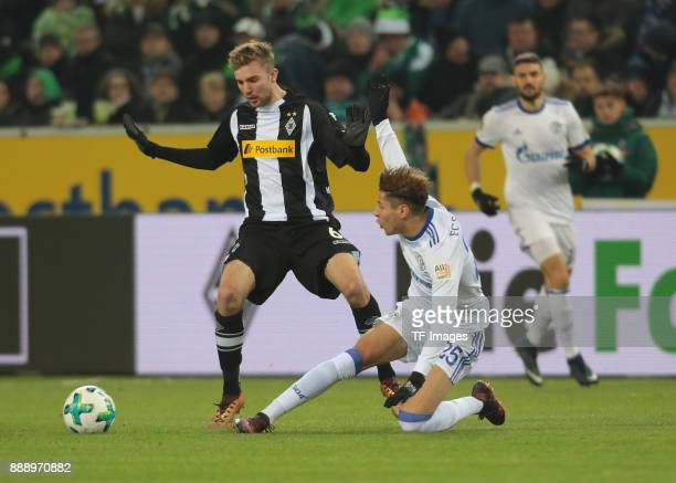 Christoph Kramer of Borussia Moenchengladbach and Amine Harit of Schalke battle for the ball during the Bundesliga match between Borussia...
