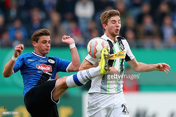 Christoph Kramer of Borussia Moenchengladbach and Tom Schuetz of Arminia Bielelfeld battle for the ball during the DFB Cup Quarter Final match...
