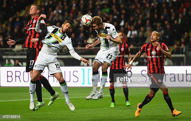 Christoph Kramer of Borussia Moenchengladbach heads the ball next to Alexander Madlung of Eintracht Frankfurt and Alvaro Dominguez of Borussia...