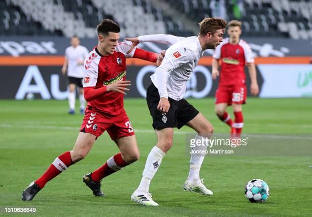 Christoph Kramer of Borussia Moenchengladbach holds off Keven Schlotterbeck of SC Freiburg during the Bundesliga match between Borussia...