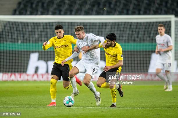 Christoph Kramer of Borussia Moenchengladbach is chased by Jadon Sancho and Mahmoud Dahoud of Borussia Dortmund during the DFB Cup Quarter Final...