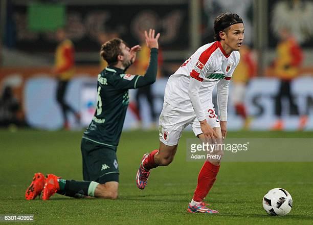 Christoph Kramer of Borussia Moenchengladbach is injured by Takashi Usami of Augsburg during the Bundesliga match between FC Augsburg and Borussia...