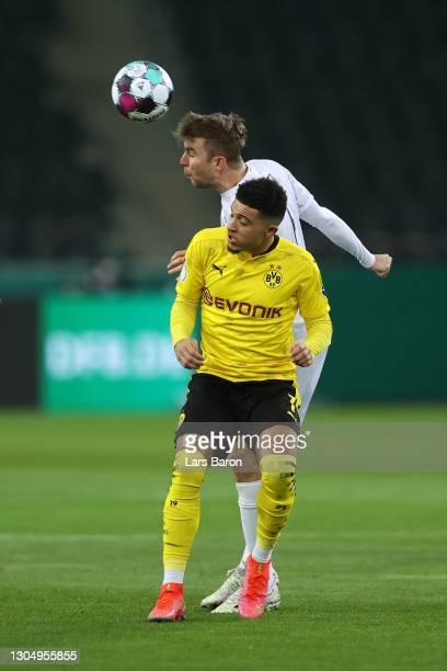 Christoph Kramer of Borussia Monchengladbach wins a header over Jadon Sancho of Borussia Dortmund during the DFB Cup quarter final match between...