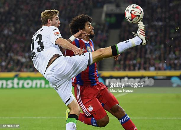 Christoph Kramer of Gladbach and Dante of Muenchen compete for the ball during the Bundesliga match between Borussia Moenchengladbach and FC Bayern...
