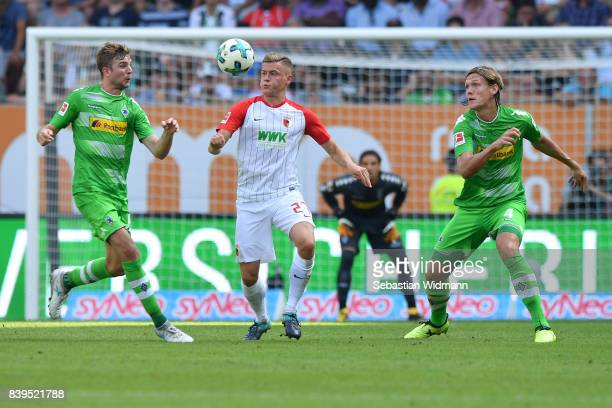 Christoph Kramer of Moenchengladbach Alfreo Finnbogason of Augsburg and Jannik Vestergaard of Moenchengladbach during the Bundesliga match between FC...