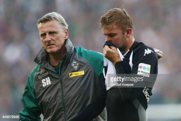 Christoph Kramer of Moenchengladbach gets lead off the pitch to be treated for an injury by Dr Stefan Hertl during the Bundesliga match between...