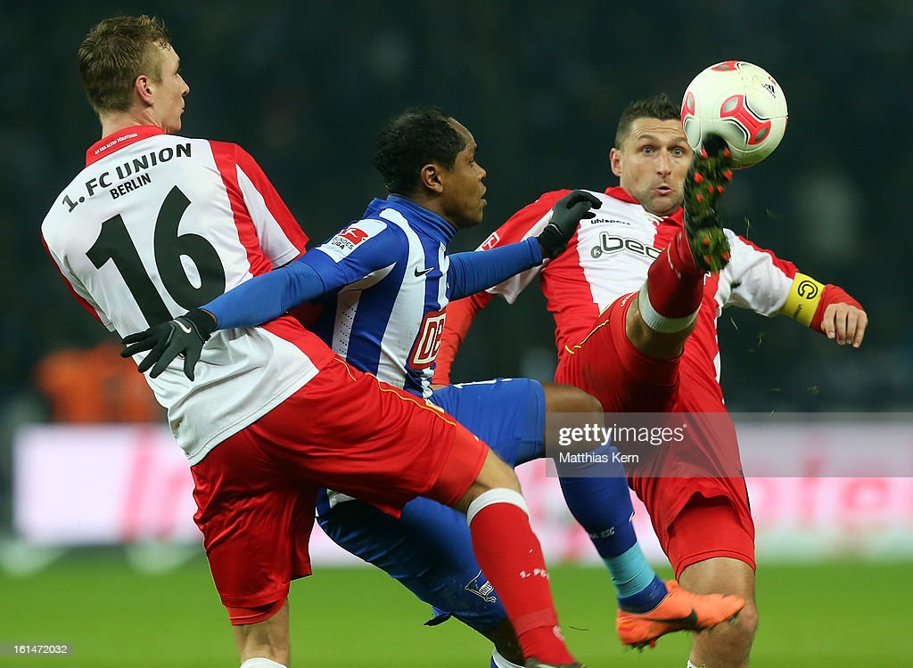 Christoph Menz, Ronny and Torsten Mattuschka (L-R) battle for the ball during the Second Bundesliga match between Hertha BSC Berlin and 1.FC Union Berlin at Olympic Stadium on February 11, 2013 in Berlin, Germany.