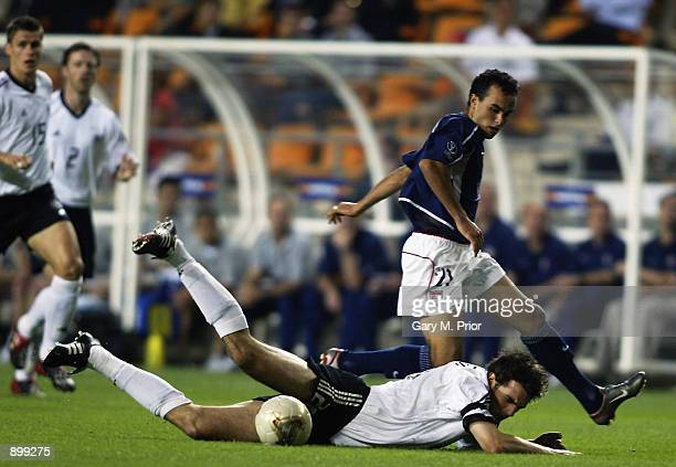 Christoph Metzelder of Germany falls under the challenge from Landon Donovan of the USA during the FIFA World Cup Finals 2002 Quarter-Finals match...
