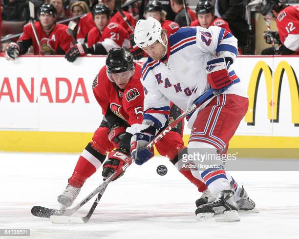 Christoph Schubert of the Ottawa Senators battles for a bouncing puck off a faceoff with Colton Orr of the New York Rangers at Scotiabank Place on...