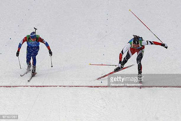 Christoph Sumann of Austria crosses the finish line to win the silver medal ahead of Evgeny Ustyugov of Russia during the men's 4 x 75 km biathlon...