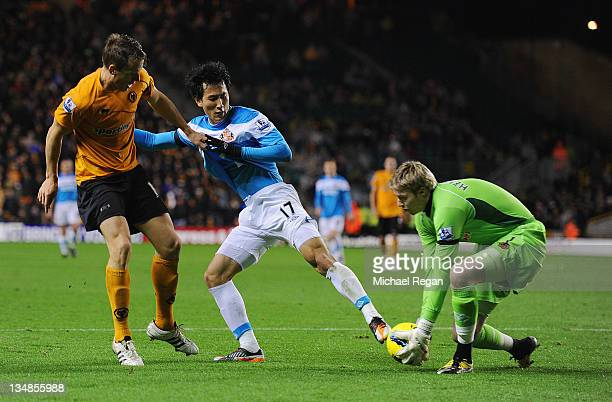 Christophe Berra and Wayne Hennessey of Wolves in action with Ji DongWon of Sunderland during the Barclays Premier League match between Wolverhampton...